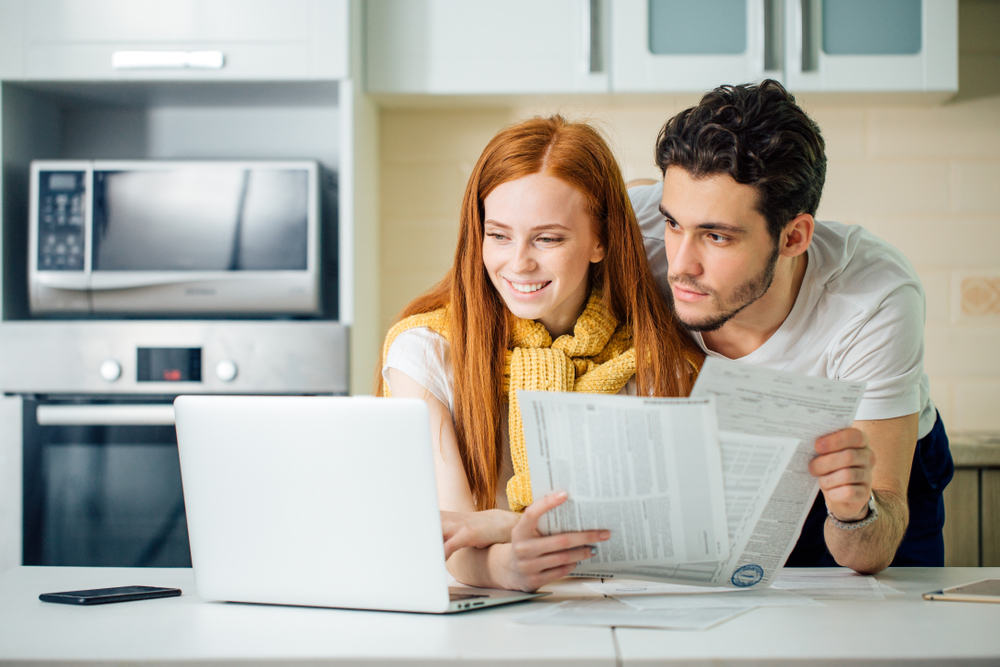 tax personal finance photo via couple looking at their finances on laptop